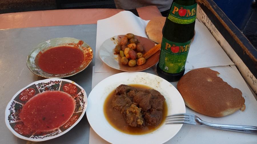 Tajine, sous de toumat, pimentinha, azeitonas, pão e refrigerante de cidra, que é bom pra caramba!
